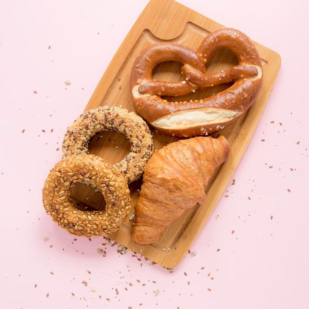Tabla de madera con pretzel y croissant Foto gratis