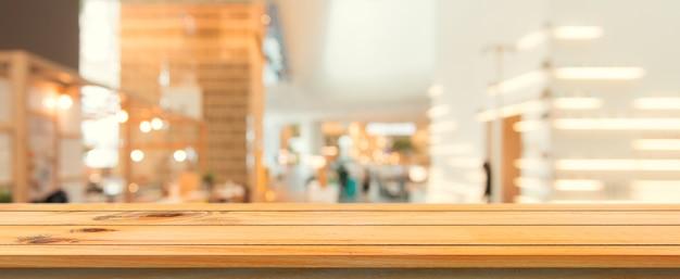 Tabla de madera tabla vacía de fondo borrosa. perspectiva mesa de madera marrón sobre desenfoque en el fondo cafetería. banner panorámico - se puede utilizar simulacro para la presentación de productos de montaje o diseño. Foto gratis