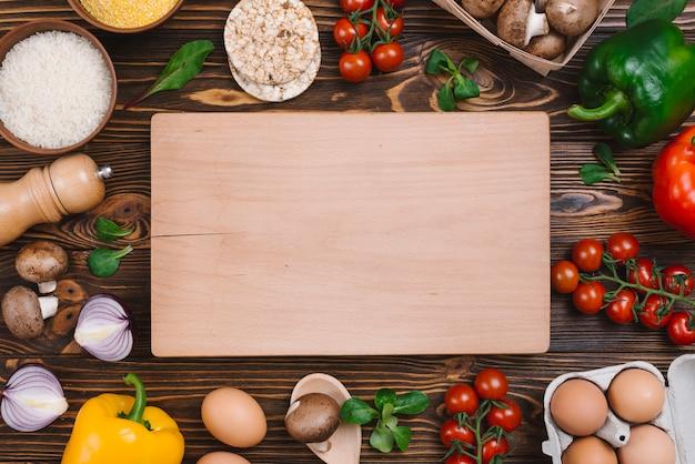 Tabla para picar rodeada de verduras; huevos y granos de arroz en el escritorio Foto gratis