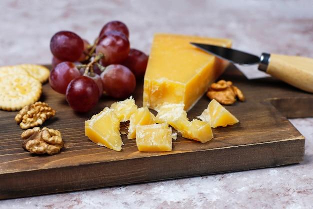 Tabla de quesos con queso duro, cuchillo de queso, copa de vino tinto, uva sobre superficie de hormigón marrón Foto gratis