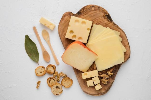 Tabla de quesos con rebanada de pan; hoja de laurel y nogal sobre superficie blanca Foto gratis