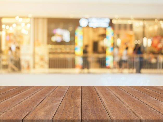 La tabla vacía del tablero de madera empañó el fondo. madera marrón perspectiva sobre desenfoque en grandes almacenes Foto gratis