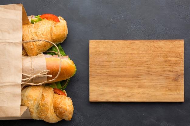 Tablero de madera en blanco y sandwiches Foto gratis