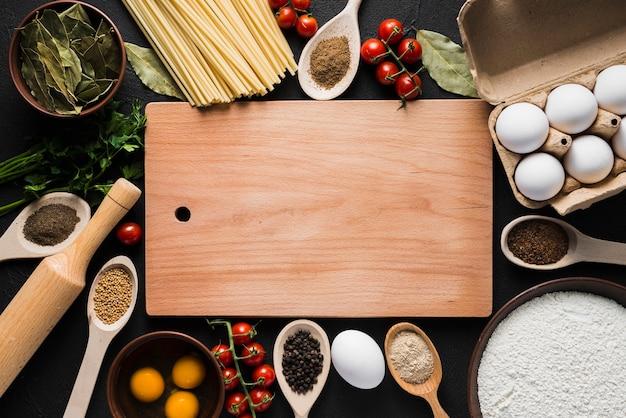Tablero en medio de ingredientes de cocina Foto gratis