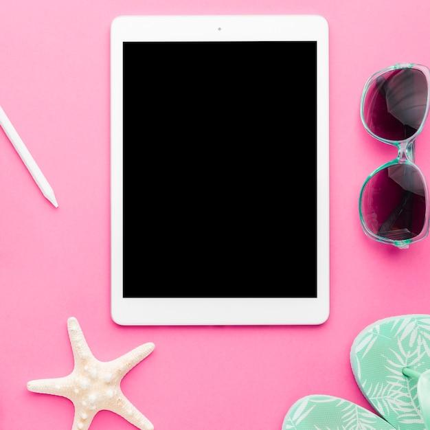 Tablet y accesorios de playa en superficie brillante. Foto gratis