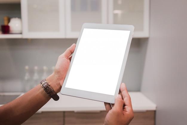 La tableta de la maqueta en hombre de negocios da la exhibición vacía en la tabla casera. Foto Premium