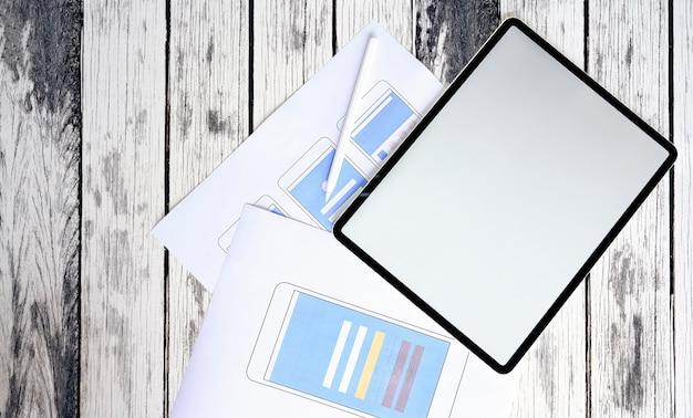 Tableta con pantalla en blanco y diseño de prototipo de teléfono inteligente en la mesa de madera. Foto Premium