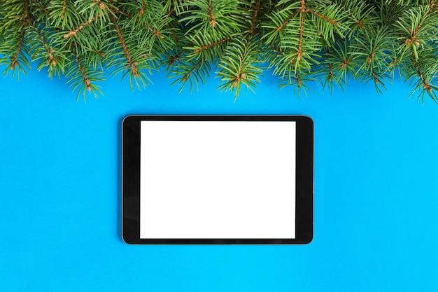 Tableta con pantalla en blanco sobre el color azul pastel. vista superior con decoración navideña Foto Premium