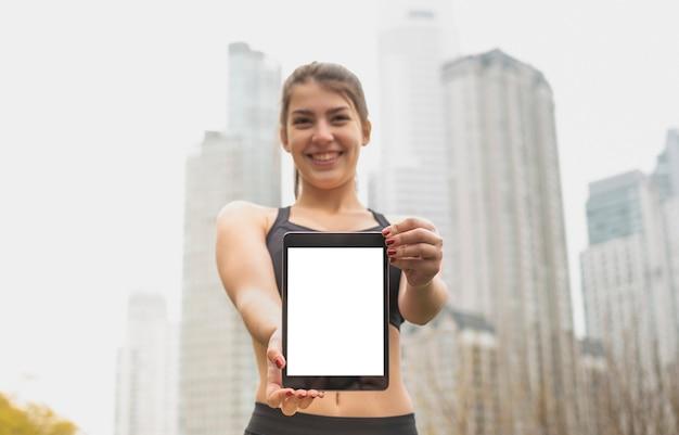 Tableta sonriente de la explotación agrícola de la chica joven Foto gratis