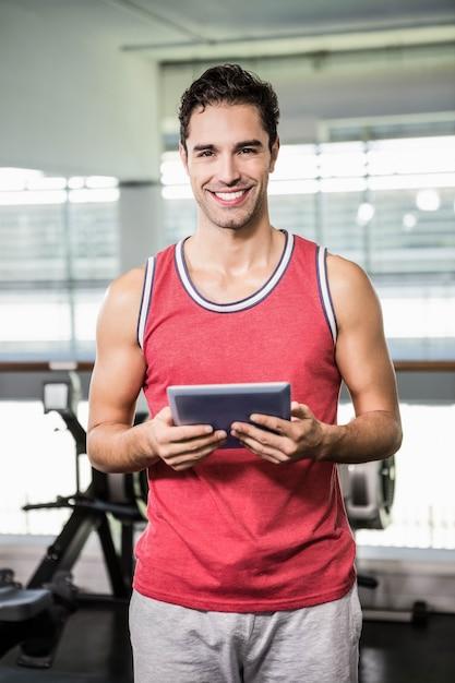Tableta sonriente de la tenencia del hombre en el gimnasio Foto Premium