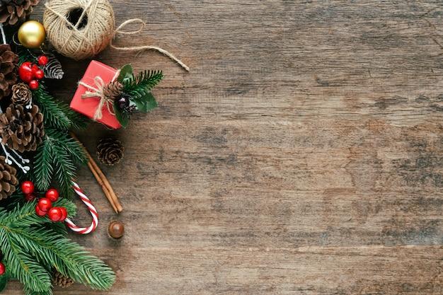Tablón de madera con hojas de pino, piñas, bolas de acebo, caja de regalo y bastón de caramelo en concepto de navidad. Foto Premium
