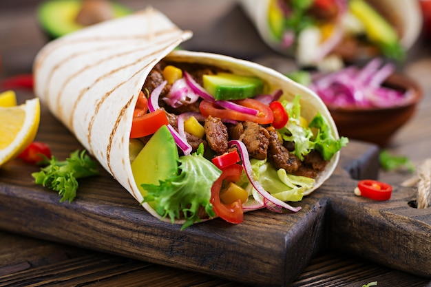 Tacos mexicanos con carne en salsa de tomate y salsa de aguacate Foto Premium