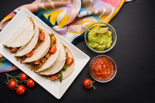 Tacos en un plato cerca de la servilleta y salsas Foto gratis