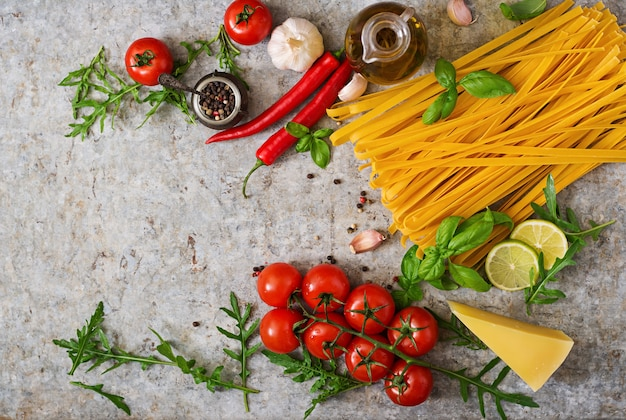 Tagliatelle de pasta e ingredientes para cocinar (tomate, ajo, albahaca, chile). vista superior Foto gratis