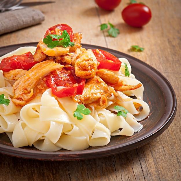 Tagliatelle pasta con tomate y pollo Foto gratis