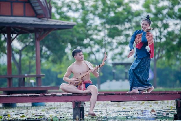 Tailandia mujeres y hombres en traje nacional con pin de guitarra (instrumento de cuerda pinchada) Foto gratis