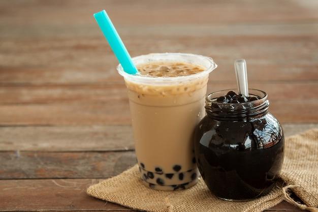 Taiwán té con leche helada y burbuja boba en el vaso de plástico y boba en el frasco de vidrio Foto Premium