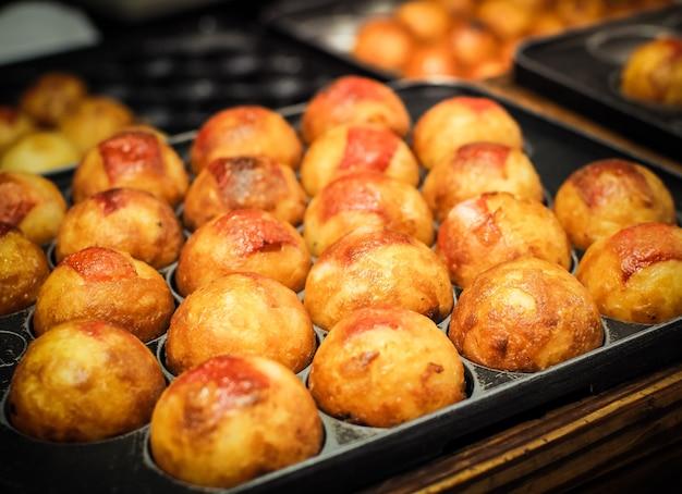 Takoyaki está cocinando en una sartén caliente. comida callejera japonesa famosa. Foto Premium
