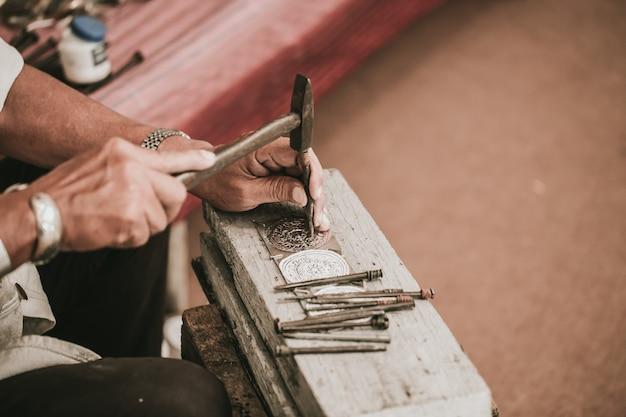 Tallador artesanal del norte de tailandia, tallador artesanal de plata con martillo y cincel para la cultura artesanal de plata en chiang mai, tailandia Foto Premium