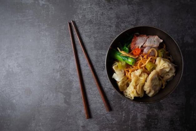Tallarines de huevo con cerdo y wonton asados rojos en la tabla. Foto gratis