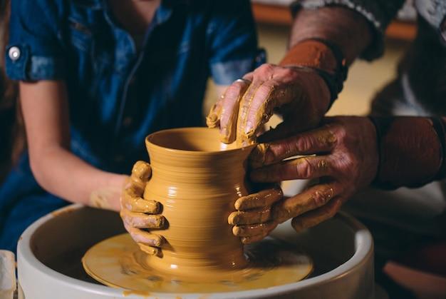 Taller de alfarería. el abuelo enseña la cerámica de la nieta. modelado de arcilla Foto Premium