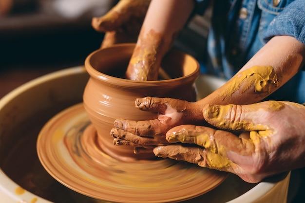 Taller de alfarería. el abuelo le enseña cerámica a su nieta. modelado de arcilla Foto Premium