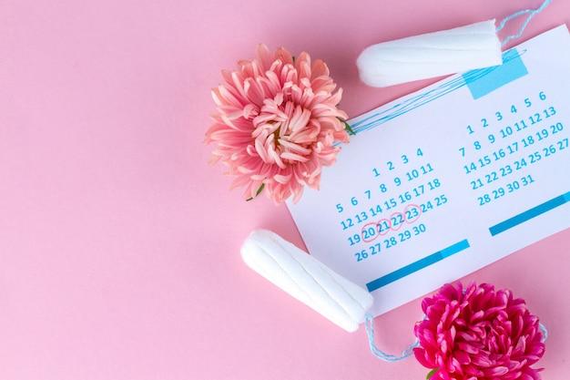 Tampones para menstruación, calendario femenino y flores. cuidado de la higiene durante los días críticos. ciclo menstrual regular Foto Premium