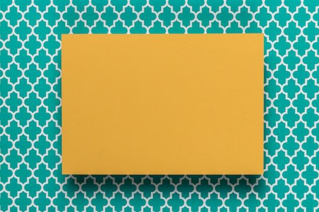 Tarjeta amarilla sobre fondo verde azulado Foto gratis