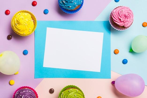 Tarjeta azul y blanca en blanco rodeada de globo; muffins y gemas sobre fondo coloreado Foto gratis