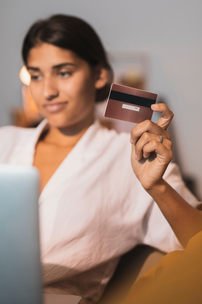 Tarjeta de crédito dorada sujeta por hermosa mujer Foto gratis