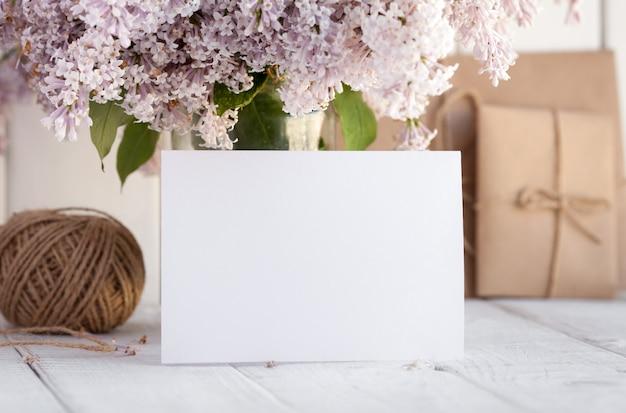 Tarjeta de felicitación blanca en blanco con flores lilas. Foto Premium