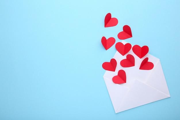 Tarjeta de felicitación del día de san valentín. corazones rojos de handmaded en sobre en fondo azul. Foto Premium