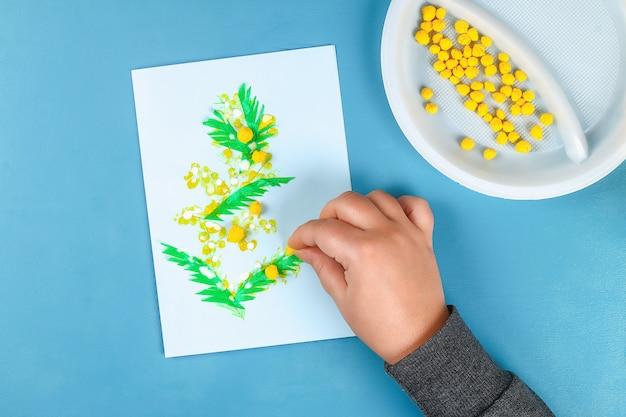 La tarjeta de felicitación de diy con la mimosa florece las bolas de papel para el 8 de marzo en fondo azul. Foto Premium