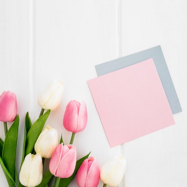 Tarjeta de felicitación y tulipanes en el fondo de madera blanco para el día de madre Foto gratis