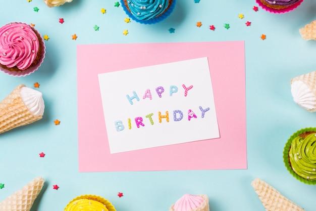 Tarjeta de feliz cumpleaños rodeada de muffins; cono de galleta y espolvoreado sobre fondo azul Foto gratis