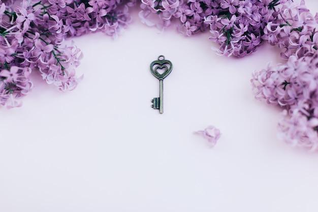 Tarjeta de papel en blanco con las flores de la lila y llave del vintage en fondo rosado. espacio para texto. estilo plano laico. Foto Premium