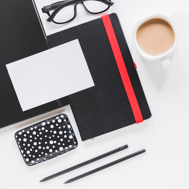 Tarjeta de presentación en cuaderno y taza de café cerca de estuche y gafas Foto gratis