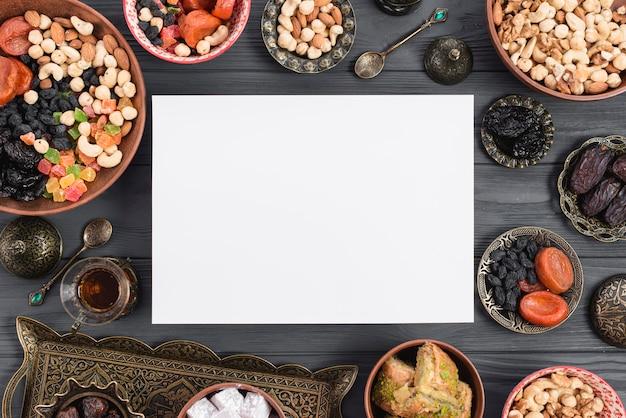 Tarjeta de ramadán rodeada de frutos secos tradicionales; fechas; té y baklava en mesa Foto gratis