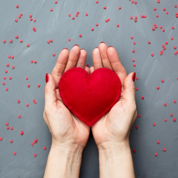 Tarjeta de san valentín con dulces corazones rojos en la mano en gris. copyspace vista desde arriba. Foto Premium