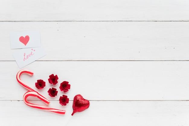 Tarjetas con inscripción de amor junto a corazón decorativo y bastones de caramelo Foto gratis