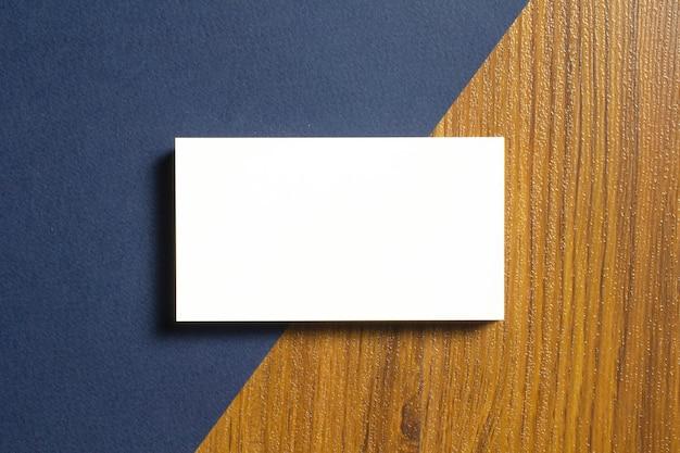 Tarjetas de visita en blanco, la mitad de cada una se acuesta sobre papel con textura azul y escritorio de madera Foto gratis