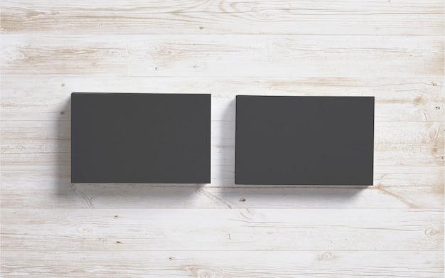 Tarjetas de visita negras en blanco sobre fondo de escritorio de madera Foto gratis
