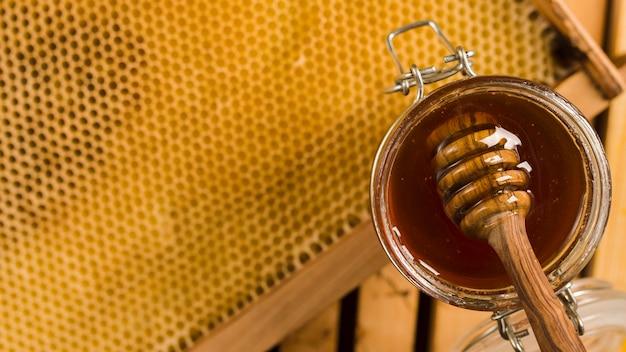 Tarro de cristal lleno de miel con cuchara de miel Foto gratis