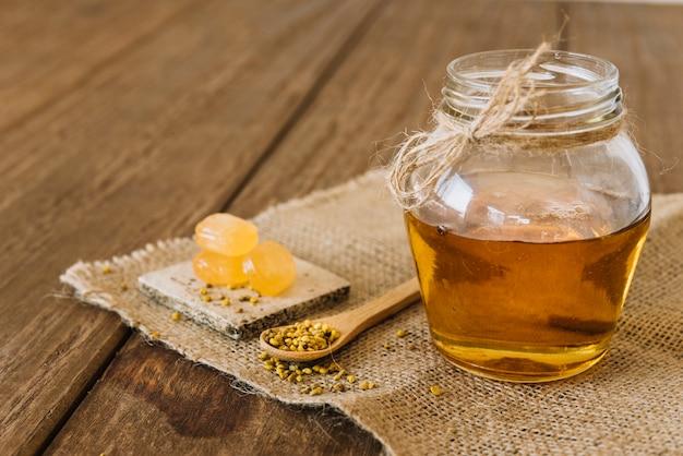 Tarro de miel con semillas de polen de abeja y caramelos en tela de saco Foto gratis