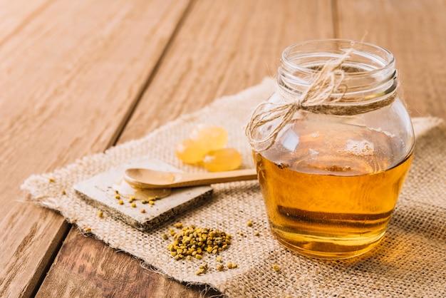 Tarro de miel semillas de polen de abeja y caramelos en tela de saco Foto gratis