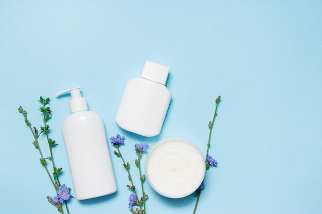 Tarros blancos de cosméticos con flores sobre un fondo azul Foto Premium