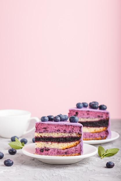 Tarta casera con crema de soufflé y mermelada de arándanos con una taza de café sobre fondo gris y rosa. vista lateral. Foto Premium