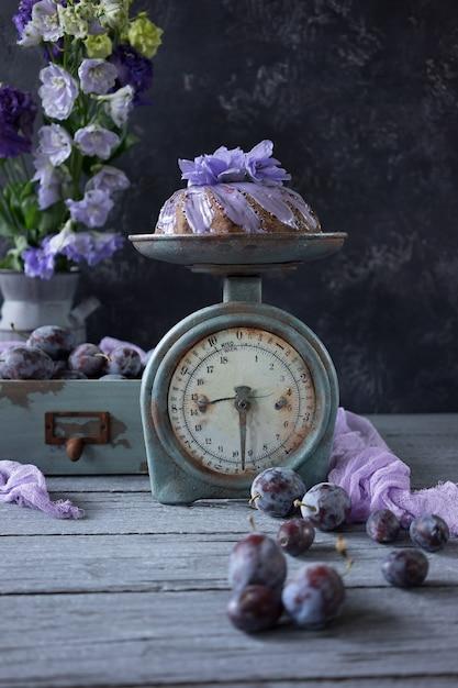 Tarta de chocolate con ciruelas y flores lilas. Foto Premium
