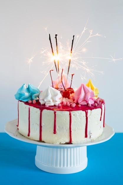 Tarta de cumpleaños con fuegos artificiales encendidos Foto gratis