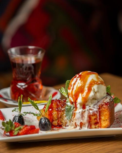 Tarta de manzana cubierta con una bola de helado adornada con uva y fresa Foto gratis